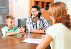 Son and father answer questions of a social worker. In home royalty free stock photography