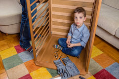Son and father assembling cot for a newborn at. Portrait of cute son assembling with his father cot for a newborn at home. Family leisure concept royalty free stock image