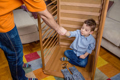 Son and father assembling cot for a newborn at. Portrait of cute son assembling with his father cot for a newborn at home. Family leisure concept stock photo