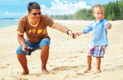 Son and father at the beach. The son asked his father to take a picture of a crab on the beach Royalty Free Stock Photography