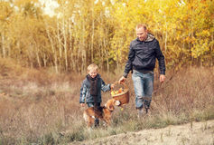 Son with father carry full basket of mushrooms in autumn forest Stock Photo