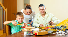 Son with father doing something with working tools, happy woman Royalty Free Stock Photo
