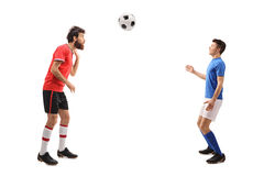 Son and a father dressed in jerseys playing with football. Full length profile shot of a son and a father dressed in jerseys playing with a football isolated on stock images