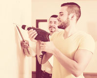 Son and father drilling wall Royalty Free Stock Photo