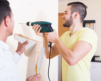 Son and father drilling wall Royalty Free Stock Photography