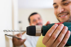 Son and father drilling wall Royalty Free Stock Image