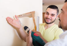 Son and father drilling wall Stock Photography