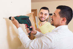 Son and father drilling wall Stock Images