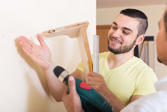 Son and father drilling wall. Young positive son and father drilling wall indoors royalty free stock image