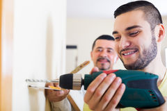 Son and father drilling wall. Young positive son and mature father drilling wall indoors stock image