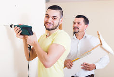 Son and father drilling wall. Young smiling son and elderly father drilling wall indoors royalty free stock image