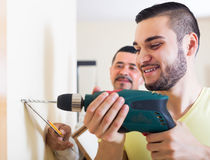 Son and father drilling wall. Young smiling son and mature father drilling wall indoors stock photo