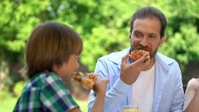 Son and father eating tasty pizza in cafe, favorite food, family weekend stock images