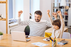 Son and father expressing triumph. Feeling success. Handsome boy watching football on the computer sitting near his father holding arms in the air royalty free stock photography