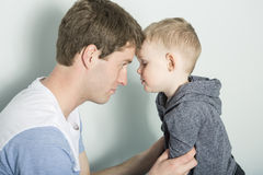 Son with father forehead to. A Son with father forehead to at home bed Stock Photography