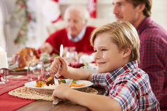 Son With Father And Grandparents Enjoying Christmas Meal royalty free stock image