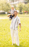 Son and father. Father holding his son on shoulder and walking through park Stock Photography