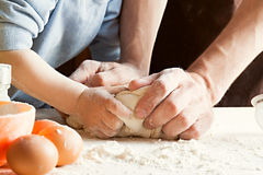 The son and father knead the dough. Cooking process Stock Photography