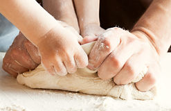 The son and father knead the dough. Cooking process Stock Images