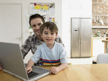Son And Father With Laptop Sitting At Table Royalty Free Stock Photo