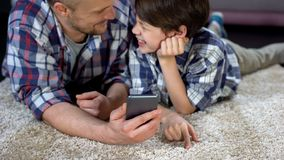 Son and father laughing after doing selfie, using new photo app in smartphone. Stock photo royalty free stock image