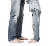 Son and father legs in tattered jeans stock images