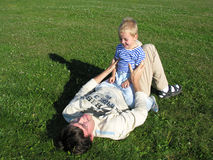 Son on father lie. On grass stock photos