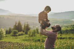 Son with father on mountain. Happy father and little son are walking in the mountains stock image