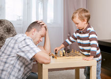 Son and father playing chess at home. Son and father playing chess in room Stock Images