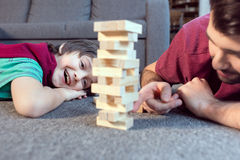 Son and father playing jenga game at home. Cheerful son and father playing jenga game at home Stock Photo