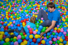 Son and father is playing. In pool of plastic balls Royalty Free Stock Photo