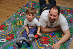 Son and father playing with toys on carpet Royalty Free Stock Photography