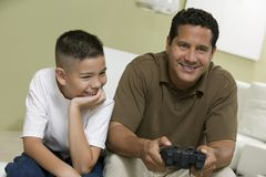 Son with father Playing Video Game on sofa in living room royalty free stock photos