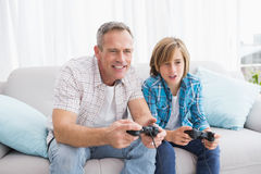 Son and father playing video games together on the couch Royalty Free Stock Photography