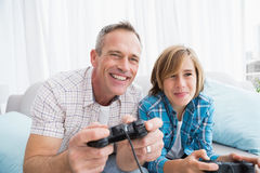 Son and father playing video games together on the couch Royalty Free Stock Images