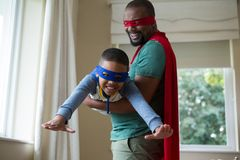 Son and father pretending to be a superhero at home. Smiling son and father pretending to be a superhero at home Stock Image