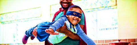 Son and father pretending to be a superhero in kitchen. At home Stock Image
