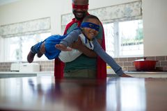 Son and father pretending to be a superhero in kitchen Royalty Free Stock Photos