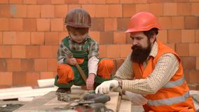 Son and father puts a brick to build a wall. Work with tools. Little son helping his father with building work. Boy play. As builder or repairer. Happy family stock video