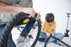 Son and father repairing bicycle tire in studio Royalty Free Stock Images