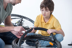 Son and father repairing bicycle tire in studio Stock Photo
