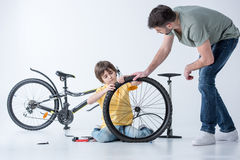 Son and father repairing bicycle tire in studio Stock Photos