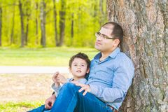 Son and father resting under a tree in the village. Father and son sit under a big tree stock image