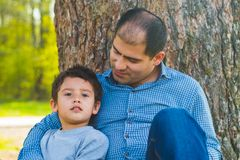 Son and father resting under a tree in the village. Father and son sit under a big tree royalty free stock photo