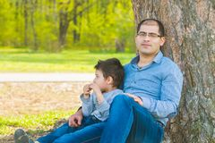 Son and father resting under a tree in the village. Father and son sit under a big tree Stock Photos