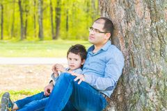 Son and father resting under a tree in the village. Father and son sit under a big tree royalty free stock image