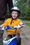 Son with father riding bike. Father helping his son learning to ride a bike stock images