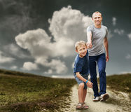 Son with father running on the footpath stock images
