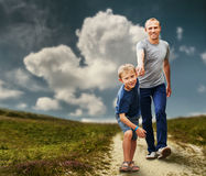 Son with father running on the footpath royalty free stock image