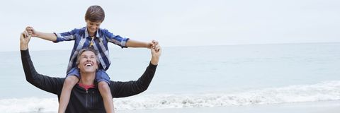 Son on father's shoulders against beach Stock Photography